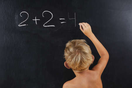 little boy without a T-shirt thinks on the blackboard, the child writes on the school chalkboard a chalk, a summer school Banque d'images - 140674252