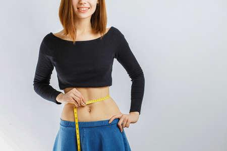 beautiful slender girl measuring waist meter on white background, diet is the best friend of girls