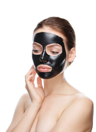 beautiful girl with black cosmetic mask on face posing on camera. mask made at home isolated on a white background
