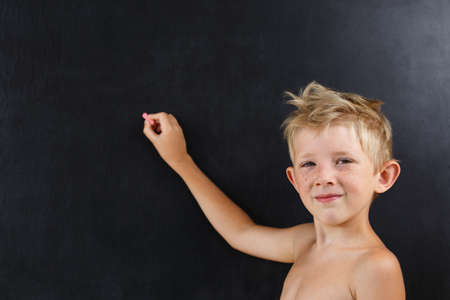 little boy without a t-shirt points at an empty blackboard, the child writes on a school chalkboard a chalk, a summer school Banque d'images - 140828647