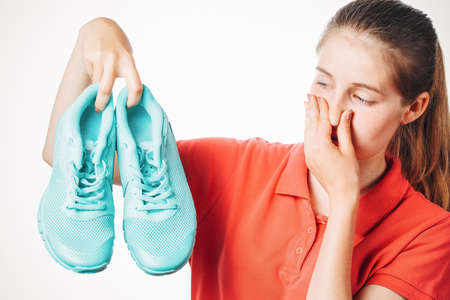 girl holds stinky sneakers and closes her hand with her nose, smell of shoes, photo on white isolated background
