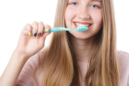 cute girl holding a toothbrush near her mouth isolated on white background, healthy teeth and proper care