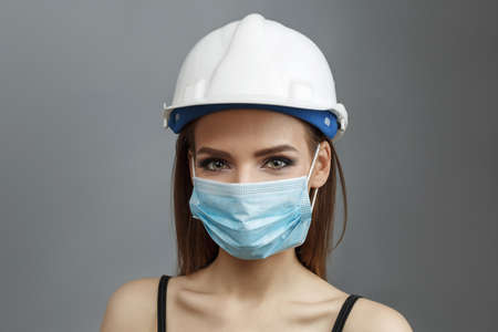 Pretty girl in medical mask and white construction helmet on a gray background.