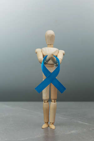 Wooden figure mannequin with blue prostate cancer ribbon on gray background. Cancer Control Concept. dark blue ribbon colon cancer symbol. Stock Photo