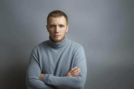 Mann schaut ernsthaft in die Kamera mit vor der Brust verschränkten Armen. Auf grauem Hintergrund. Studiofoto.