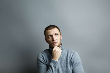 Man thoughtfully put his hand to his chin. Pensively looking to the side. Thinking about something. On a gray background. Standard-Bild