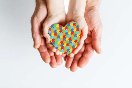 Male hands hold childrens palms with puzzle pattern heart in them. The concept of family love and support On light background. World Autism Awareness day