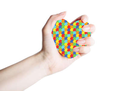 female hand with puzzle pattern heart on palm isolated on white background. mental health care concept. World Autism Awareness day 写真素材