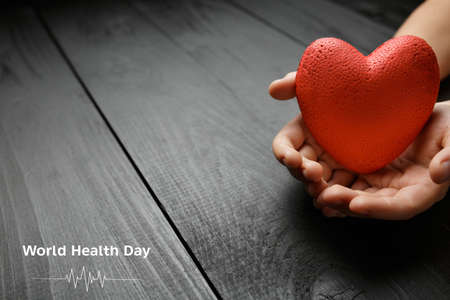 world health day. red heart in hands on a dark background, the concept of love and care for loved ones and needy