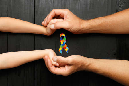 puzzle or jigsaw pattern ribbon in hand on black wooden background. concept of helping those in need. World Autism Awareness day