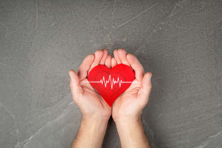 world health day. red heart in hands on gray background, the concept of love and care for loved ones and needy.
