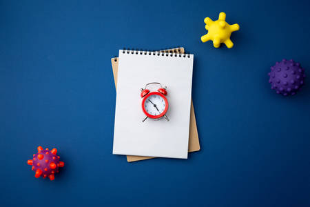 Spiral notebook with virus abstract strain model and red alarm clock on blue background close up flat lay. Pandemic protection concept against coronavirus top view.