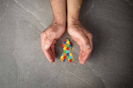 jigsaw pattern ribbon in hand on gray background, symbol of the fight against autism. concept of helping those in need World Autism Awareness day 写真素材