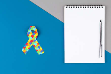 Autism ribbon on open notebook isolated on blue and gray background, mental health care concept. Flat lay. World Autism Awareness day