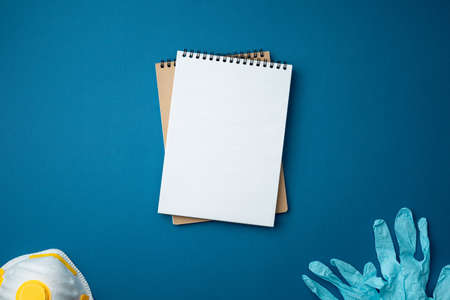 Spiral notebook with surgical gloves and face mask on blue background close up flat lay. Pandemic protection concept against coronavirus top view.