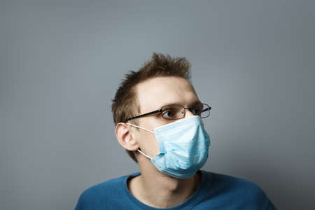 Young man with glasses and a medical mask on gray isolated background. Concept for the prevention of viral diseases. Studio photo.. european guy wearing respirator mask, Coronavirus and covid-19 conce 写真素材