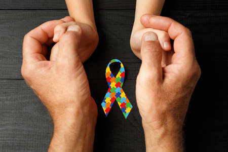 puzzle ribbon in hand on black wooden background. concept of helping those in need. World Autism Awareness day Stock Photo
