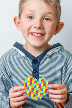 child holds jigsaw pattern heart with both hands In striped sweater on gray background. World Autism Awareness day