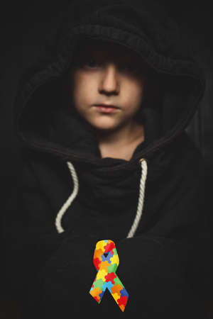 child with puzzle ribbon on dark background. boy holds the symbol of the fight, concept of helping those in need. World Autism Awareness day Stock Photo