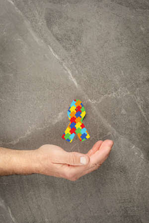 puzzle pattern ribbon in hand on gray background, symbol of the fight against autism. concept of helping those in need World Autism Awareness day