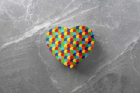 jigsaw pattern heart on gray stone background top view. World Autism Awareness day