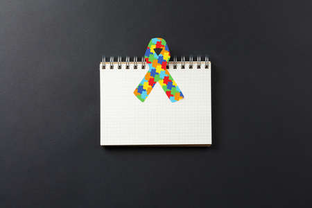 jigsaw pattern ribbon on open notebook isolated on black background, mental health care concept. Flat lay. World Autism Awareness day