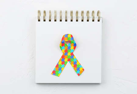 jigsaw pattern ribbon on open notebook isolated on white background, mental health care concept. Flat lay. World Autism Awareness day
