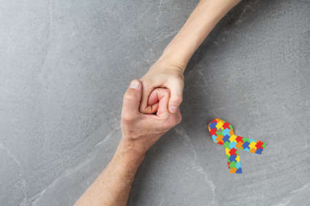 jigsaw ribbon with hands clasped together on gray background, mental health care concept. concept of helping those in need World Autism Awareness day
