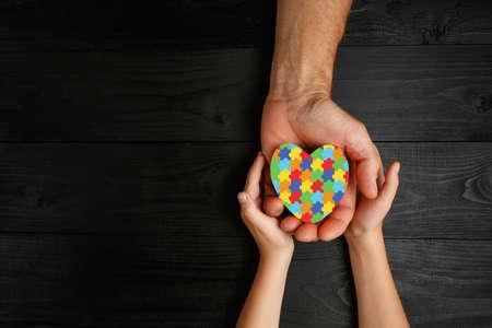 jigsaw pattern heart in hands on dark background. World Autism Awareness day Archivio Fotografico