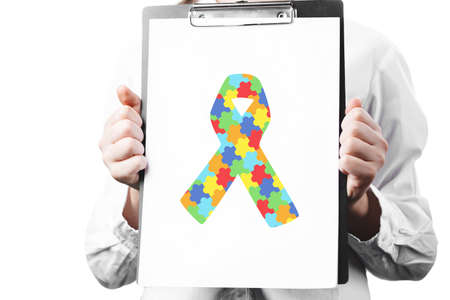 woman doctor holding tablet with puzzle ribbon. World Autism Awareness day. symbol combating cancer and AIDS, isolated on white background. Day against HIV and Cancer