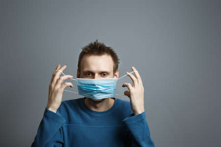 Man puts on a medical mask. Prevention of viral diseases of the common cold and flu. Gray background. Studio photo.. european guy wearing respirator mask, Coronavirus and covid-19 concept Stock Photo