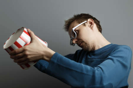 Man in white 3D glasses finished eat popcorn watching a movie in the cinema. Gray isolated background. Stock Photo