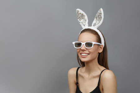 Beautiful smiling girl with rabbit ears in white 3d glasses on gray background. Easter holiday concept  studio photo  beauty makeup.