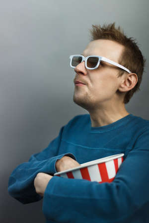 Man disabled in white 3D glasses eats popcorn emotionally watching a movie in the cinema. Man without arm watch tv on gray isolated background.