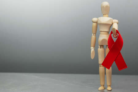 Wooden figure doll holds red ribbon. Cancer Control Concept. Symbolizing the day of AIDS and HIV. On a gray background.