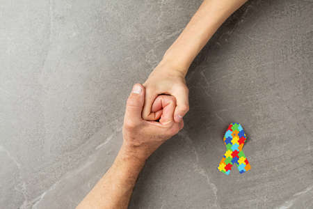 puzzle ribbon with hands clasped together on gray background, mental health care concept. concept of helping those in need World Autism Awareness day