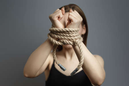 Woman with tied hands with the rope on gray background studio photo. Concept of violent action Human trafficking Kidnapping