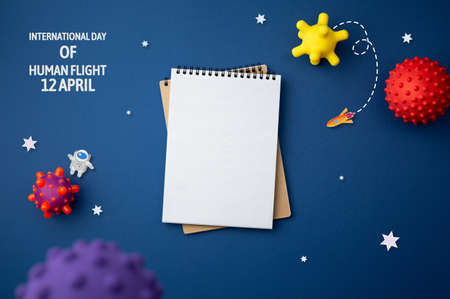 International day of human space flight. 12 April World Cosmonautics Day. Spiral notebook on abstract isolated blue background. Cartoon galactic concept. Banque d'images