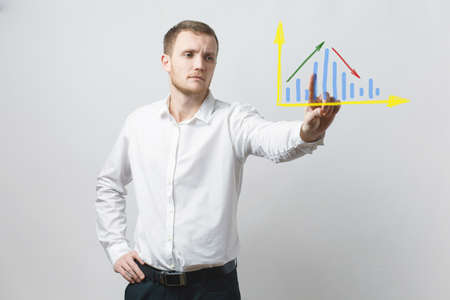 Businessman points his finger at a graph drawn on a glass board. Serious man in a white shirt and black pants on a gray isolated background. Stock Photo