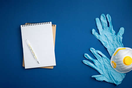Spiral notebook with surgical gloves, thermometr and respiratory face mask on blue background close up flat lay. Pandemic protection concept against coronavirus top view.