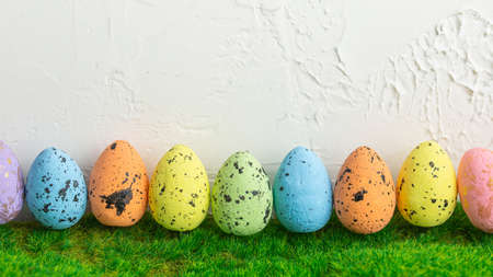 Row of colorful eggs in green grass with a white grunge background. Easter holiday. Spring nature concept.