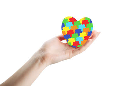 female hand with jigsaw pattern heart on palm isolated on white background. mental health care concept. World Autism Awareness day Stock fotó