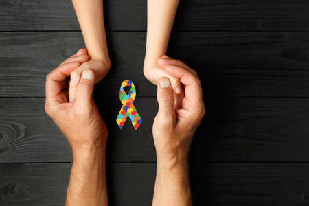 puzzle ribbon in hand on black wooden background. concept of helping those in need. World Autism Awareness day 版權商用圖片