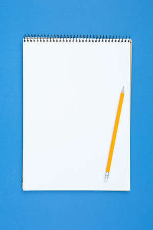 Spiral notebook and pencil with an eraser on a blue isolated background. Design concept with copy space for notes. Blank page for business text. School notepad Top view. Vertical photo.