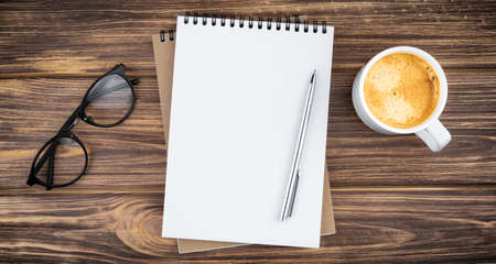 Spiral notebook with pen, glasses and coffee cup on a wooden background. Design concept with copy space for notes. Blank page for business text. Office notepad. Top view.
