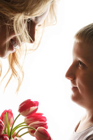 Mother and son with bouquet of flowers. little boy gives flowers to mom. White isolated background, backlite photo. International Mothers Day, woman day March 8th. Holiday Gift Concept. Zdjęcie Seryjne