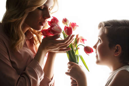 daughter gives flowers to mom. woman and little girl with  bouquet of flowers on white isolated background, backlite photo. International Mothers Day, March 8th. woman day Concept.