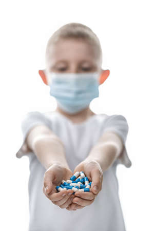 Little boy in medical mask holds handful of pills on white isolated background. Backlight vertical Photo. Healthcare and medical concept. Prevention of virus infection coronavirus or Covid 19.