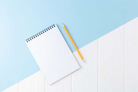 Spiral notebook with a pencil on a blue background. Design concept with copy space for notes. Blank page for business text. School notepad Top view. Foto de archivo