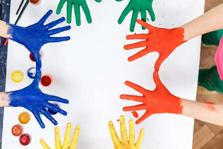 hands in paints on the background of a light table painted in different colors, children's hands soiled in gouache paint top view Standard-Bild